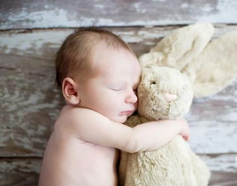 baby cuddling stuffed bunny