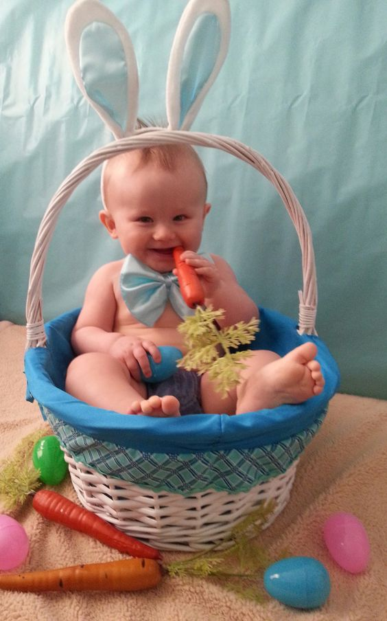 baby in basket chewing on a carrot