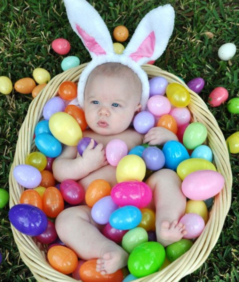 baby in basket with easter eggs and bunny ears