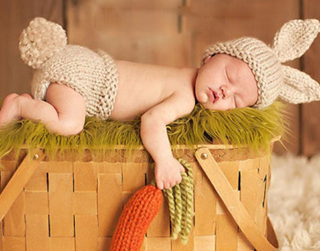 baby sleeping holding a carrot