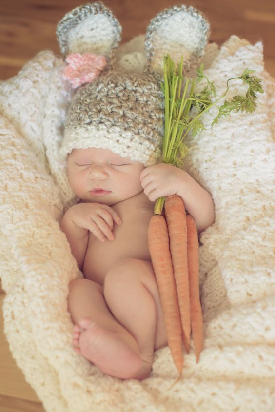 sleeping newborn with bunny hat holding carrots
