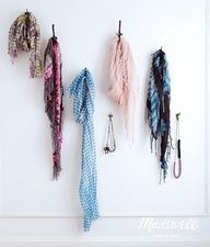 scarves and necklaces on walls with hooks